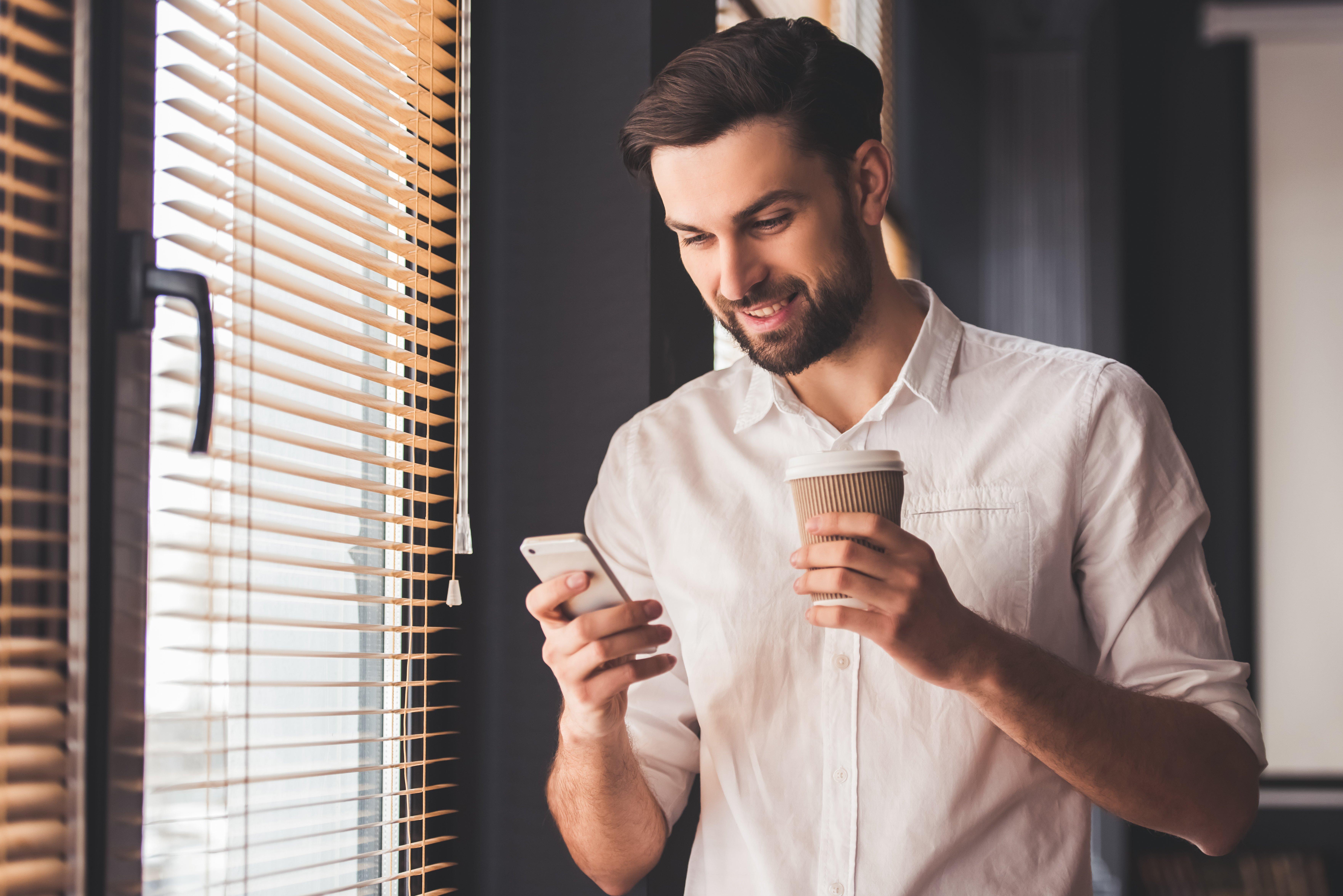 hombre firma desde su smartphone en una cafetería. la firma electrónica la puedes usar donde y cuando quieras.